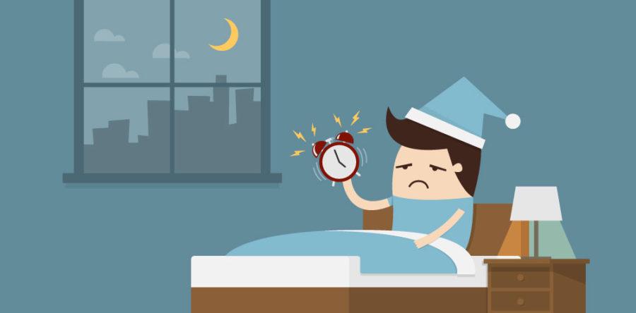persona despertándose por el insomnio con un reloj en la mano